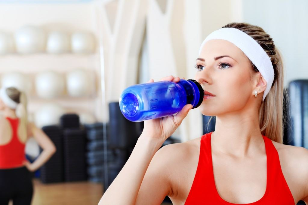 A lady drinking water after resistance training